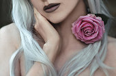 Young beautiful woman with rose fine art portrait