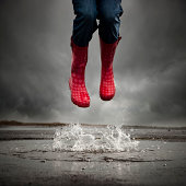 Young woman with rubber boots jumping in puddle,low section
