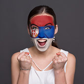 Face of young happy woman painted with flag of Serbia. Football or soccer team fan, sport event, faceart and patriotism concept. Studio shot at gray background, copy space