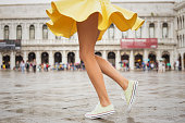 Cheerful young woman with sexy legs and yellow skirt dancing