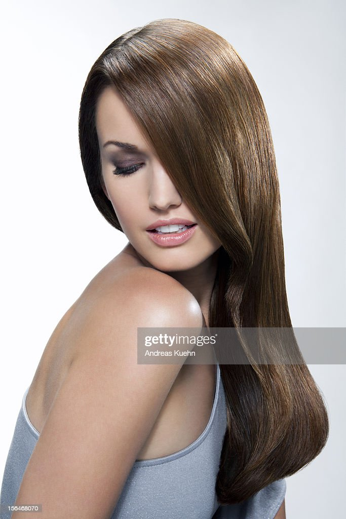Young woman with shiny hair looking over shoulder.