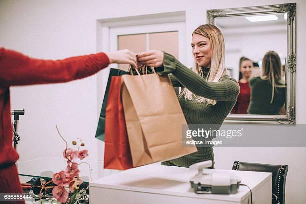 Mujer joven con bolsas de compras en la tienda de ropa