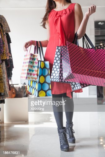 Young woman with shopping bags at fashion store