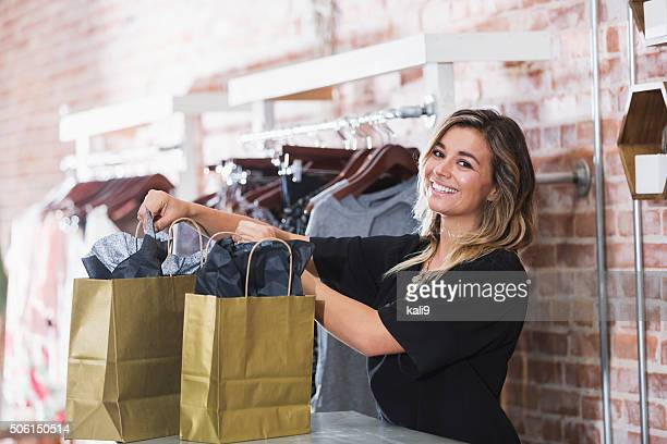 Young woman with shopping bags in clothing store