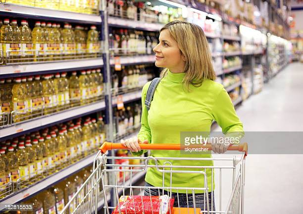 Young woman with shopping trolley strolling at a supermarket.