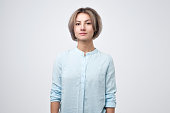 Young woman with short hairstyle wearing blue t-shirt standing with neutral expression. Photo for passport.