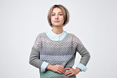 Young woman with short hairstyle wearing sweater standing with neutral expression.