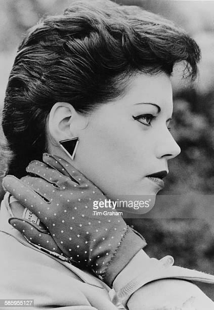 A young woman with short sweptback hair and wearing polka dot gloves and triangular earrings circa 1980