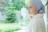 Young woman with skin cancer standing on a drip in hospital