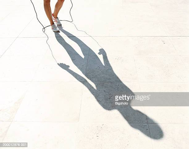 Young woman with skipping rope, low section