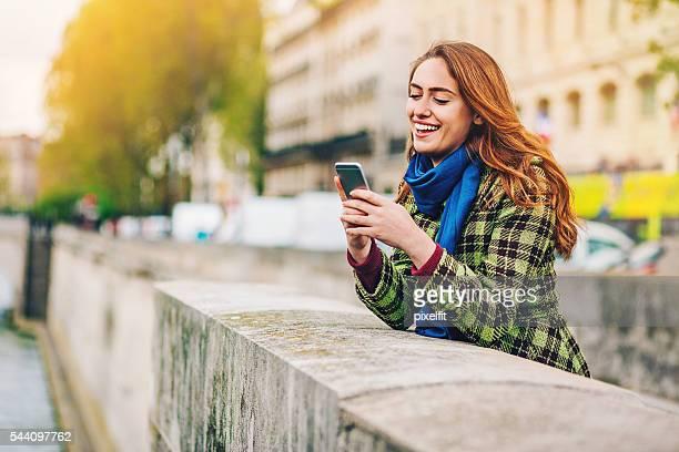 Jeune femme avec smartphone sur la Seine, à Paris