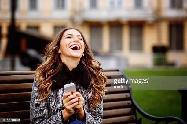 Junge Frau mit Smartphone hat großartige Zeit