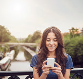 Young woman with smart phone on bridge.