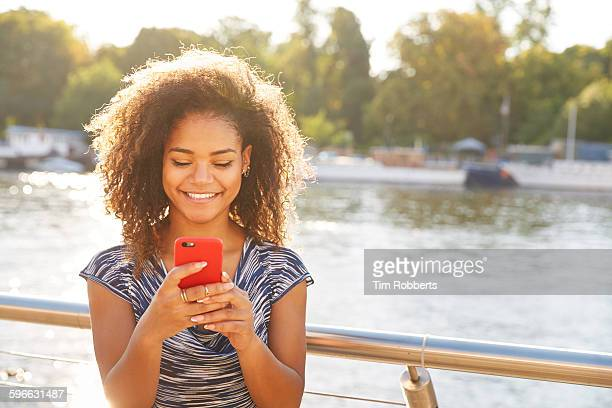 Young woman with smartphone next to river.