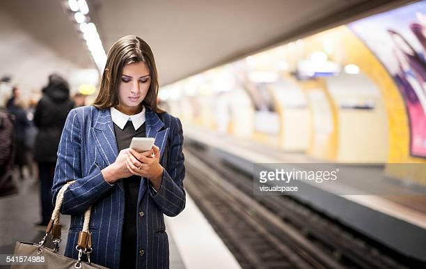 Jeune femme avec un Téléphone intelligent attente pour le métro