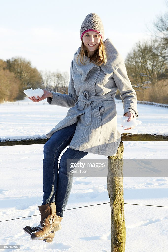 Young woman with snowballs on fence : Stock-Foto