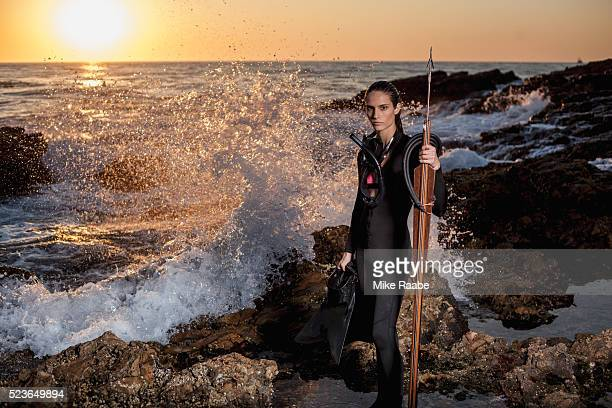 Young woman with speargun on rocky beach, Palos Verdes Peninsula, Los Angeles County, California, USA