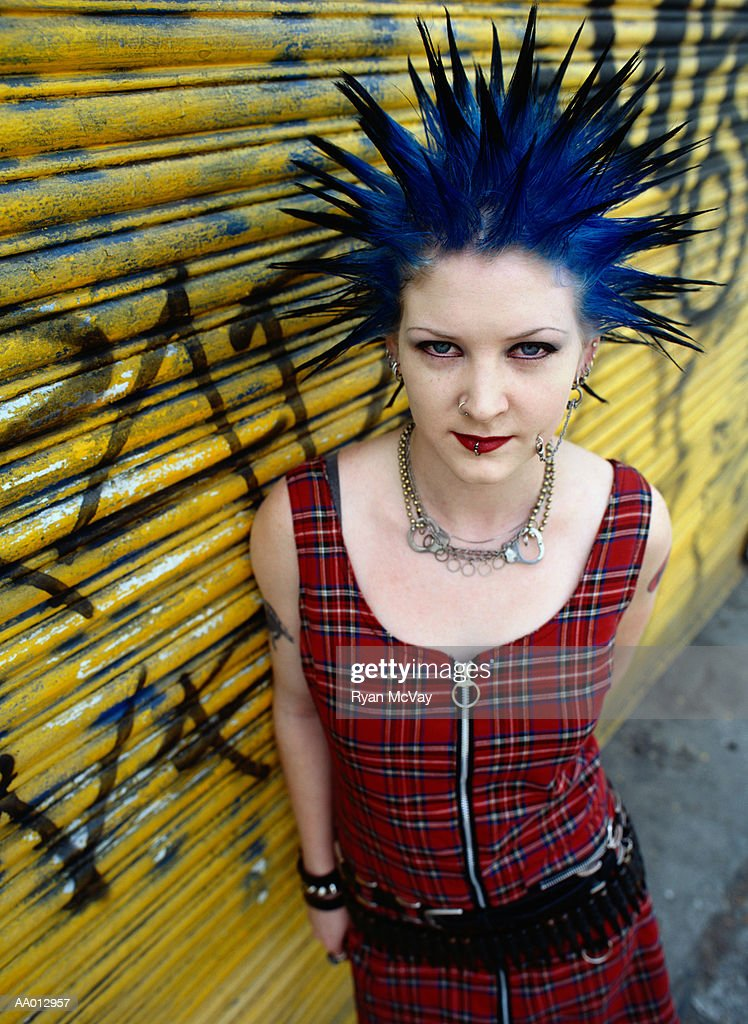 Young woman with spiked hair leaning against garage door, portrait : Stock Photo