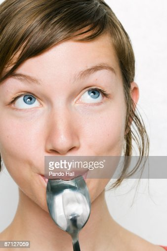 Young woman with spoon in mouth, looking up