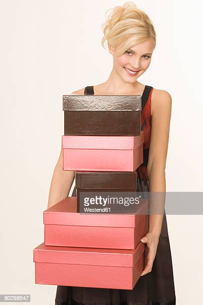 Young woman holding stack of shoe boxes, smiling, portrait
