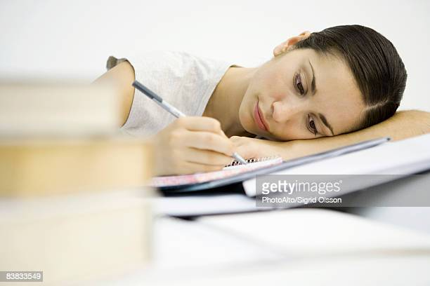 Young woman with stacks of books, writing in notebook, head resting on arms