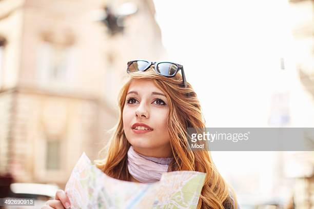 Young woman with street map looking lost, Rome, Italy