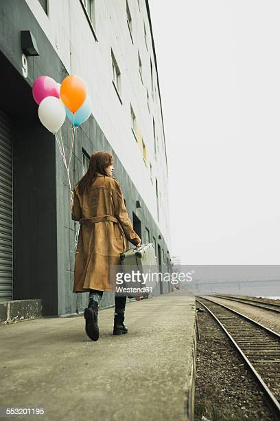 Young woman with suitcase holding bunch of balloons on platform