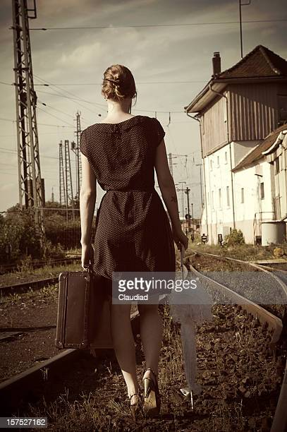 Young woman with suitcase on tracks