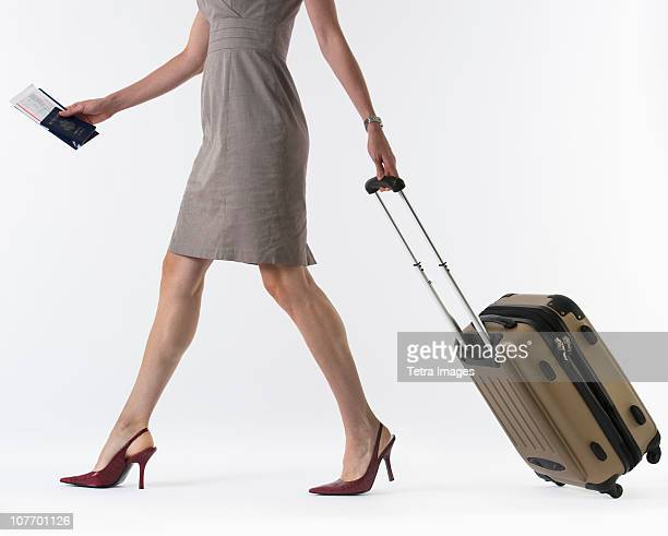 Young woman with suitcase, studio shot
