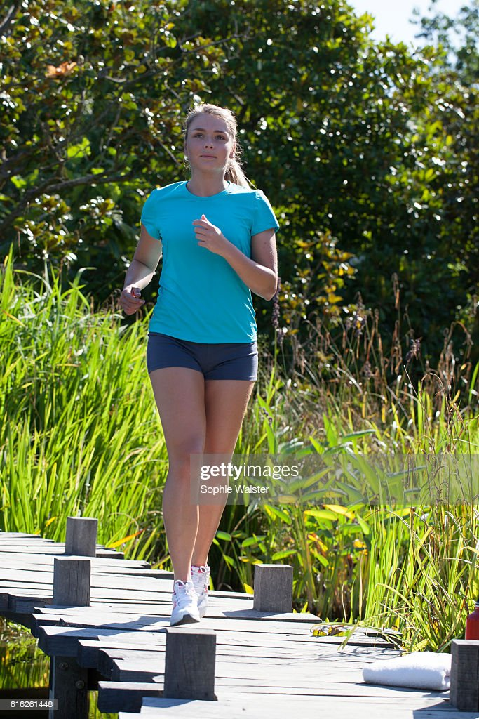 young woman with summer shorts running in natural park outdoors : Stock Photo