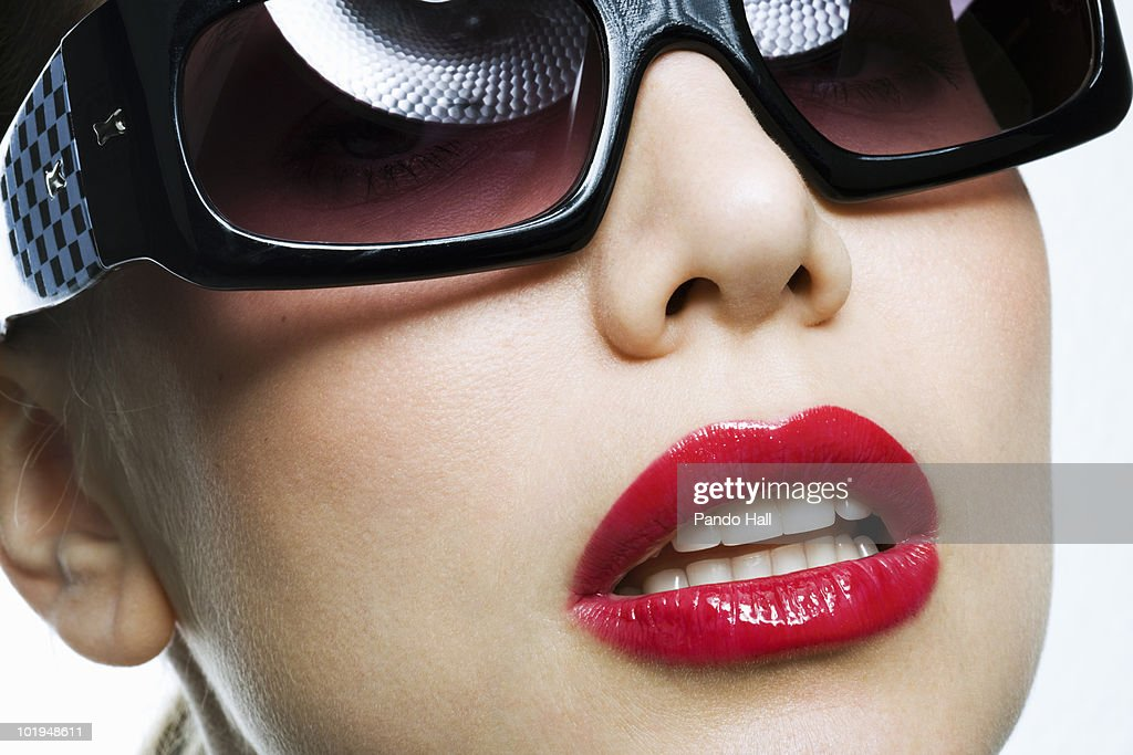 Young woman with sunglasses and red lips, close-up : Stock Photo