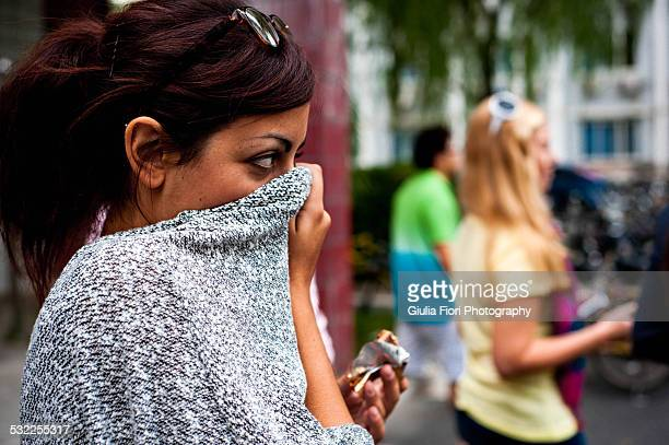 Young woman with sweater over her nose