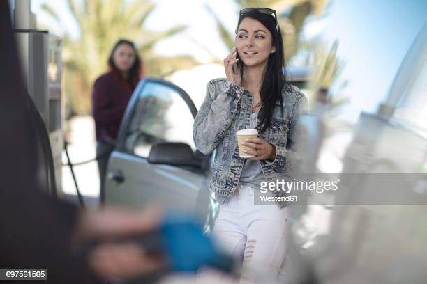 Young woman with takeaway coffee and cell phone at gas station