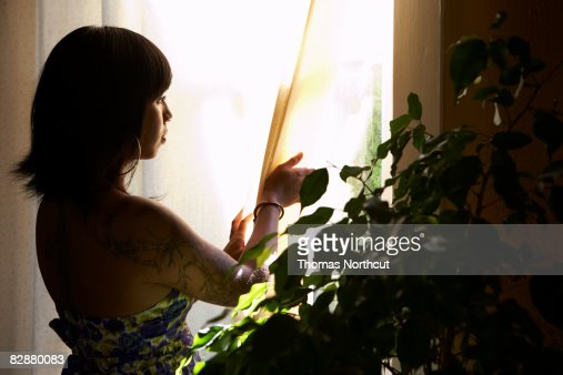 Young woman with tattoo looking out window : Stock Photo