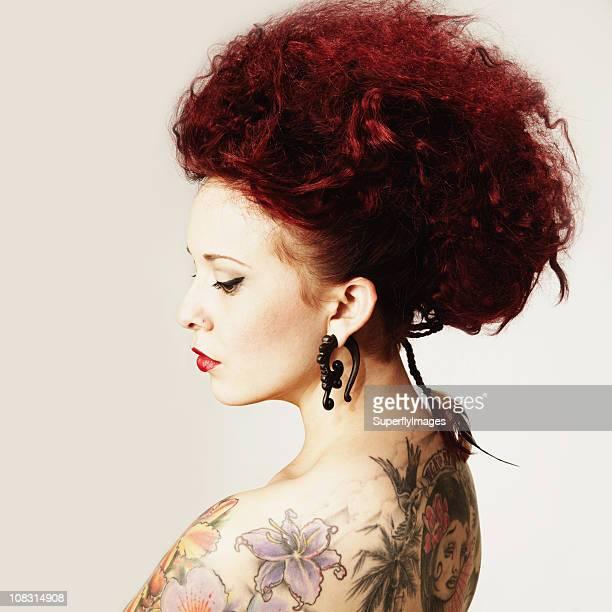 若い女性、タトゥーやトライバルイヤーリング。絶縁型