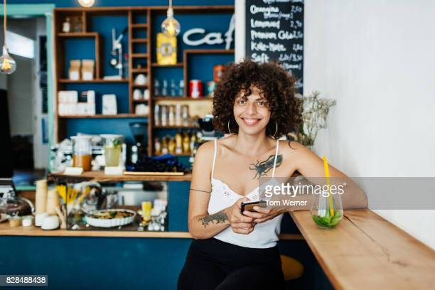 Young Woman With Tattoos Enjoying Drink In Cafe