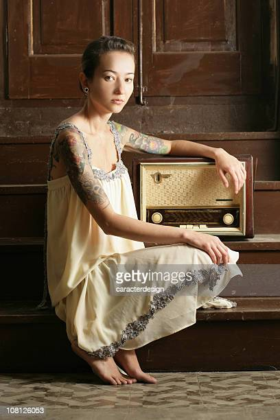Young Woman with Tattoos Sitting by Vintage Radio