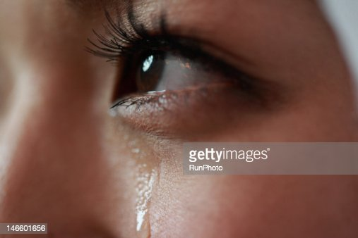 Young woman with tear rolling down cheek