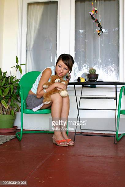 Young woman with teddy bear sitting on porch