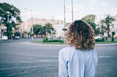 Young woman with thick curly hair looking at the european paving stone ring road. Rear view of unrecognizable female wearing blue shirt standing outside on summer day on the background of old city.