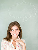 Young woman with thought bubble on blackboard, smiling