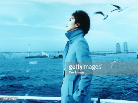 Young woman with Tokyo city in background, a flock of seagulls : Stock Photo