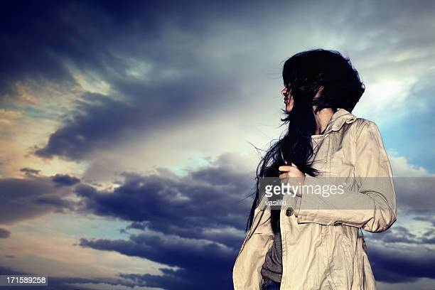 Young woman with trench coat against a dark moody sky