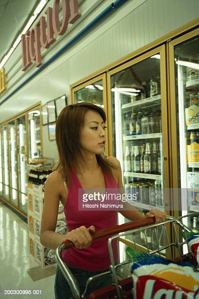 Young woman with trolley in supermarket