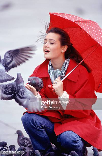 Young woman with umbrella feeding pigeons