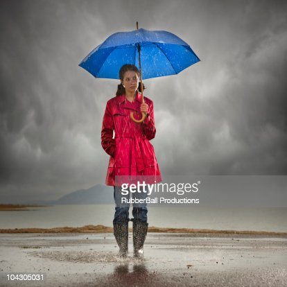 Young woman with umbrella splashing in puddle