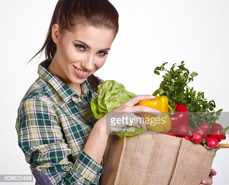 Young woman with vegetables and fruits in shopping bag : Stock Photo