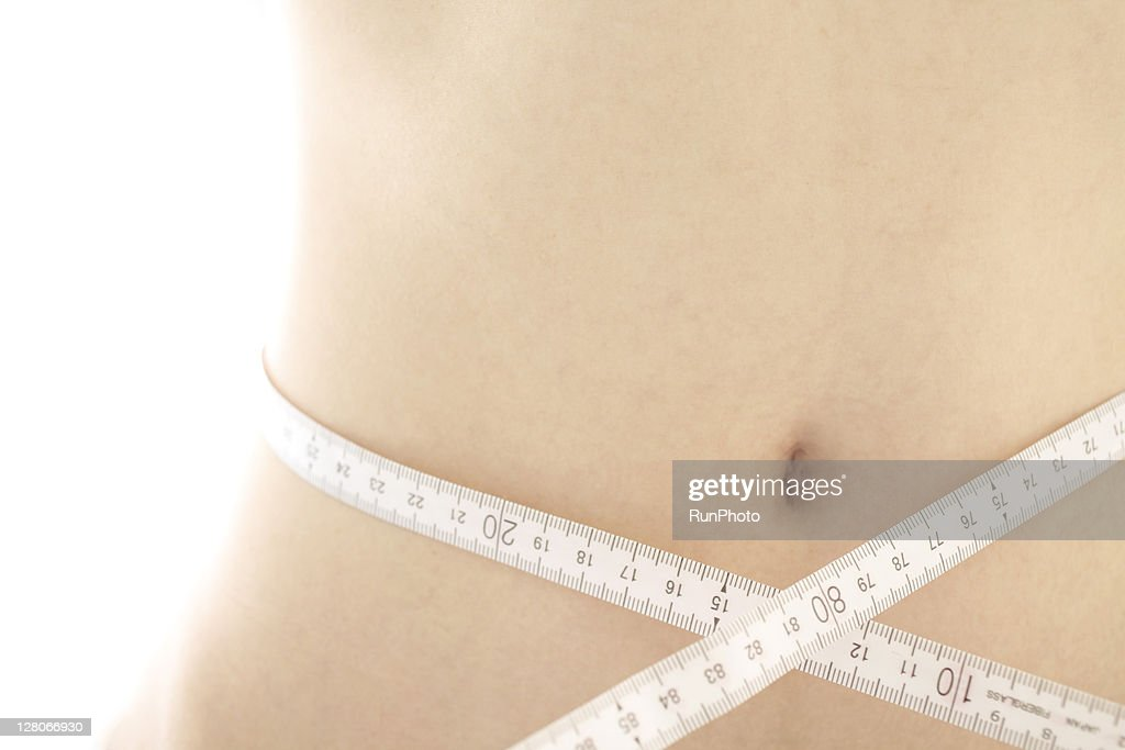 Young woman with waist wrapped in measuring tape : Stock Photo