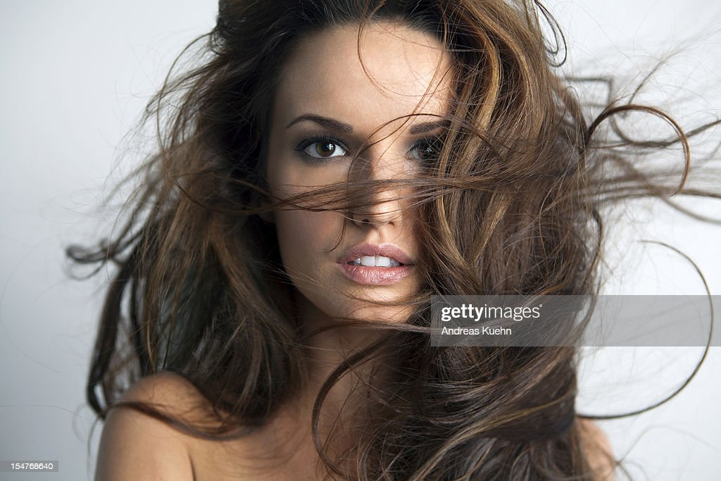 Young woman with wind blown hair across her face.