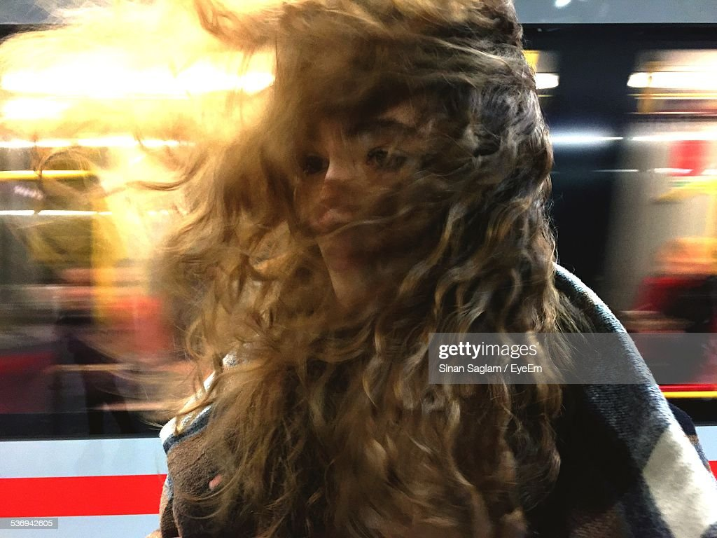 Young Woman With Wind Swept Hair At Railroad Station Against Train